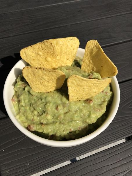fertige Guacamole als Dip in Schale mit Nachos