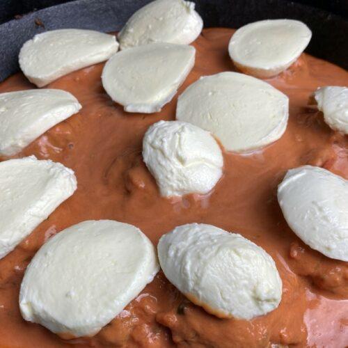 Mozzarellascheiben auf Hackbällchen in Gusspfanne